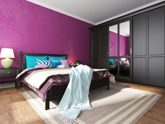 Hotel bedroom interior with black furniture, a rug and pillows on a bed and a wardrobe with a mirror on the floor with carpet
